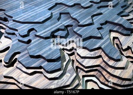 Layers of carved wood for terrain imitation model, viewed in full frame, close-up from high angle. Blue and natural wood colors - Stock Image