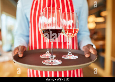 Hands of a waiter carry a tray with glasses of wine in the bistro or pub - Stock Image