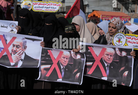 Palestinian women hold crossed-out placards depicting U.S. President Donald Trump and Israeli Prime Minister Benjamin Netanyahu during a protest against Bahrain's workshop for U.S. peace plan, in southern Gaza Strip. - Stock Image