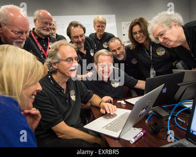 Members of the New Horizons team gather around a laptop and smile as they review new processed images from the New - Stock Image