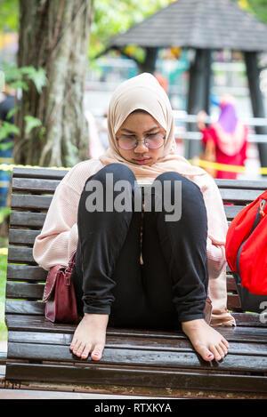 Young Malaysian Woman Reading on a Park Bench, KLCC Park, Kuala Lumpur, Malaysia. - Stock Image