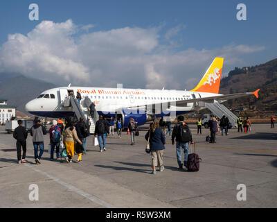 Tourists boarding aircraft on the runway at Paro Airport, Bhutan - Stock Image