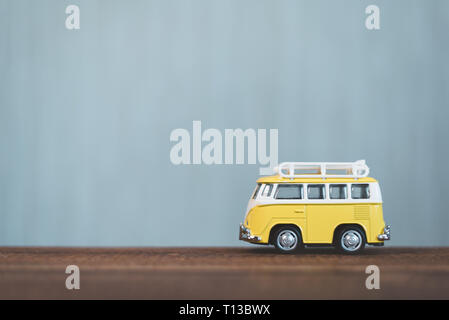 Yellow vintage miniature van on a wooden table. Concept of travel and transportation. Shallow Depth of field with selective focus - Stock Image