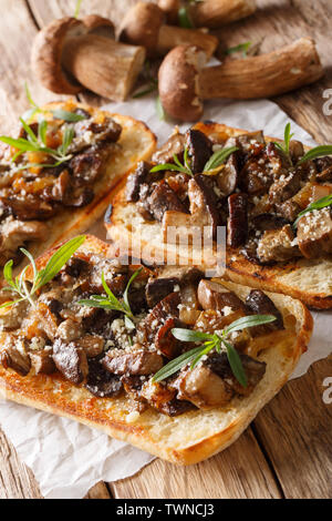 Sandwiches with fried porcini mushrooms, caramelized onions and thyme close-up on the table. vertical - Stock Image