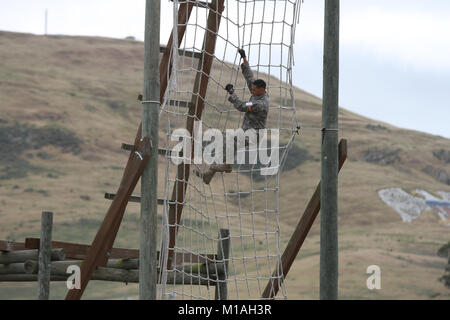 California Army National Guardsman Spc. David Chang descends a cargo net in the obstacle course event May 16 during - Stock Image