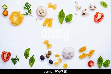 Various vegetable and ingredients for cooking pasta menu sweet basil ,tomato ,garlic ,extra virgin olive oil ,parsley  and champignon setup on white w - Stock Image