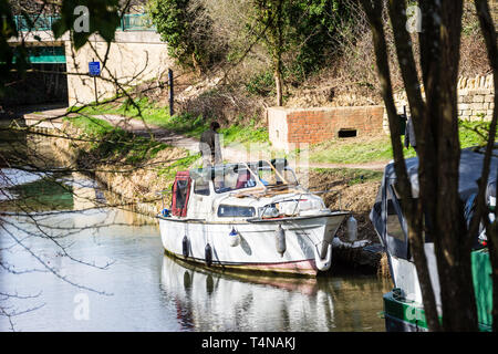 A man stood behind a small old and worn river cruiser boat moored on the Kennet and Avon canal in front of old world war 2 pill box. - Stock Image