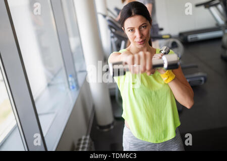 Young beautiful woman doing exercises with dumbbell in gym - Stock Image