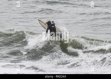 Mousehole, Cornwall, UK. 8th Feb, 2019. UK Weather. Surfers were out making most of the waves brought on by storm Erik close into the coast at Mousehole this lunchtime. Credit: Simon Maycock/Alamy Live News - Stock Image