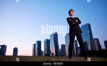 Businessman standing with his arms crossed against buildings in city at night - Stock Image