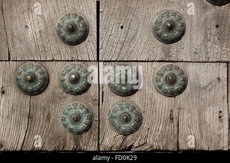 Old wooden gate fixed with large brass rivets in Albayzin district in Granada, Andalusia, Spain. - Stock Image
