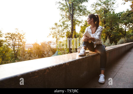 Lovely young student girl sitting outdoors, studying, holding book - Stock Image