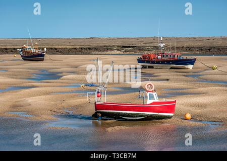 Lifeboard boats marooned on sandbanks at low tide on East Fleet river estuary at Wells next the sea, North Norfolk coast, East Anglia, England, UK. - Stock Image