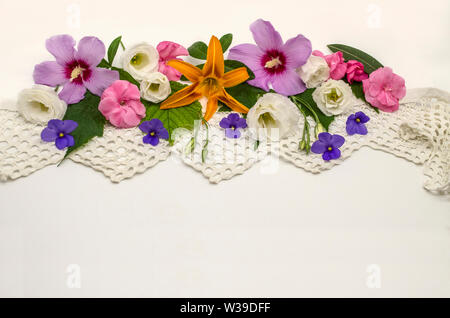 White background with openwork border,located at the top, covered with heads of flowers of purple hibiscus, white Lisianthus, raspberry oleander and v - Stock Image