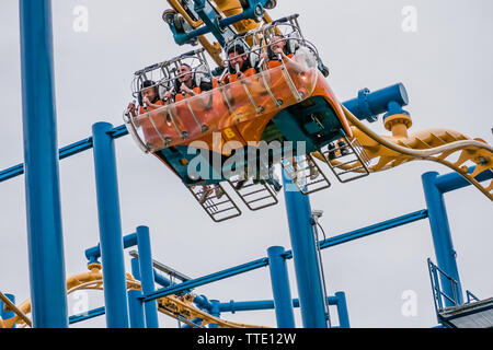 people lyding down instead of sitting down on the flying coaster ride time wrap - Stock Image