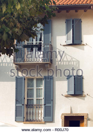 House with blue shutters - Stock Image
