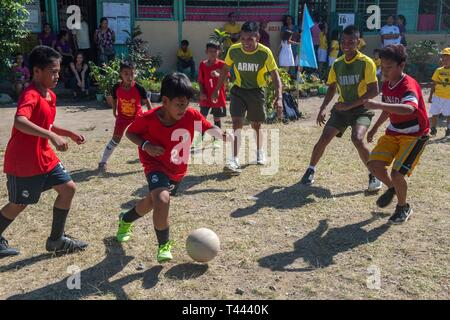 TACLOBAN, Philippines (March 14, 2019) – Members of the Armed Forces of the Philippines play soccer with San Fernando Central School students during a Pacific Partnership 2019 host nation engagement where participants played sports and interacted with students. Pacific Partnership, now in its 14th iteration, is the largest annual multinational humanitarian assistance and disaster relief preparedness mission conducted in the Indo-Pacific. Each year the mission team works collectively with host and partner nations to enhance regional interoperability and disaster response capabilities, increase  - Stock Image