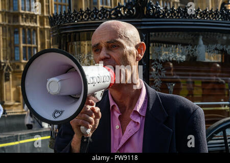 London, UK. 13th October 2018. Donnachadh McCarthy of Stop Killing Cyclists speaks briefly as the of the funeral procession of cyclists behind a horse-drawn hearse to highlight the failure of governments from all the major parties to take comprehensive action on safer cycling stops for the die-in in front of the Houses of Parliament. Stop Killing Cyclists call for £3 billion a year to be invested in a national protected cycling network and for urgent action to reduce the toxic air pollution from diesel and petrol vehicles which kills tens of thousands of people every year, and disables hundred - Stock Image