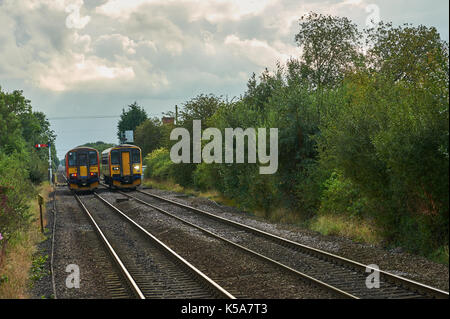 East Midlands Trains passenger trains passing at the small Lincolnshire village of Swinderby - Stock Image