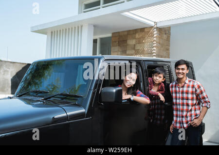 family with kid sitting in a car in car port of their house ready to go - Stock Image