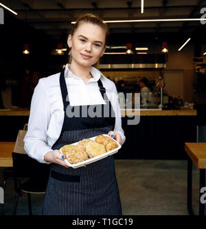 Friendly waitress welcoming customers at restaurant door. Adult young woman greeting customers and inviting to taste meatballs. Small family restauran - Stock Image