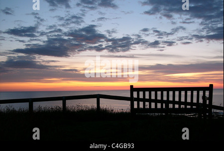 A bench seat bears witness to the sunrise at the coast - Stock Image