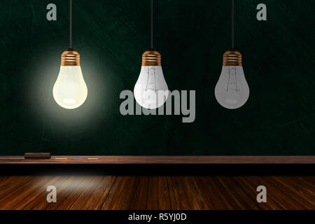 One illuminated light bulb among three in a classroom with background chalk board and wooden table and copy space. Concept of ideas, creativity and in - Stock Image
