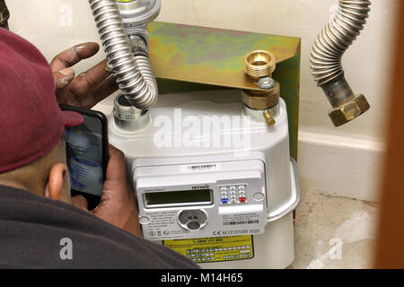 Unidentified installer fitting a new gas 'smart meter'. - Stock Image