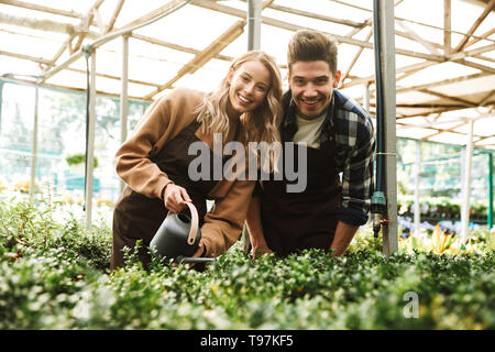 Photo of emotional happy young two colleagues gardeners at the workspace over plants. - Stock Image