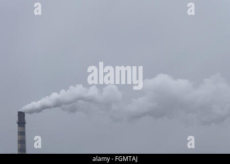 Chimney thermal power plant running on coal pollutes the air. - Stock Image