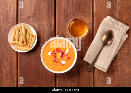 Salmorejo, Spanish cold tomato soup, overhead shot on a dark rustic wooden background with wine and picos, typical breadsticks - Stock Image