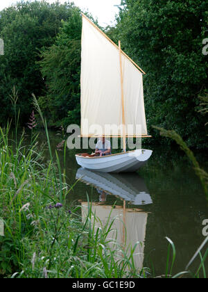 Man in a sail boat on the Kennet and Avon Canal, Devizes, Wiltshire, UK - Stock Image
