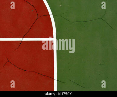 Pole aerial image of an outdoor basketball court. Includes pavement cracks, red key, white lines and green surface. - Stock Image