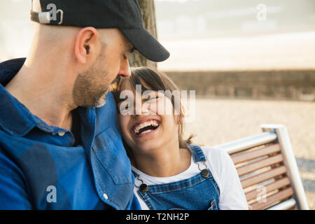Father and daughter sitting on a bench on the waterfront having fun together in a sunny day - Stock Image