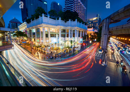Creative high angle night shot of Ratchaprasong Intersection and Erawan Shrine in Bangkok, Thailand, with colourful light trail from cars driving past - Stock Image