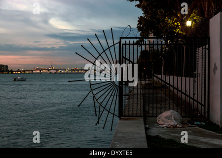 Homeless person sleeping rough at sunrise along the seawall on Biscayne Bay in Miami, Florida, USA. - Stock Image