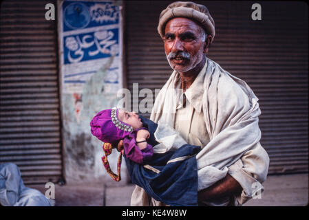 A man carrying his grandchild, Lahore - Stock Image