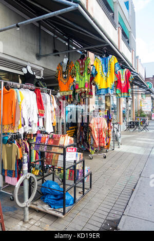 Colourful clothes hang outside on sidewalk along Baldwin st. in Kensington Market in downtown Toronto, Ontario, - Stock Image