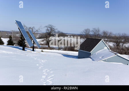 Earth sheltered home with solar photovoltaic panels in a winter rural setting. - Stock Image