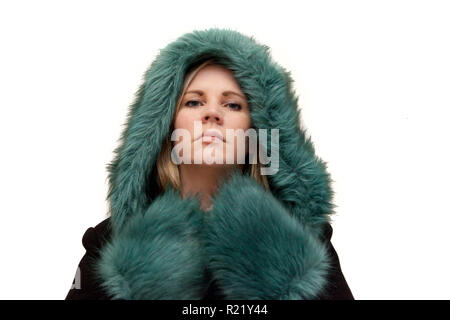 Blonde model in a beautiful green and black fur coat with serious face is ready for winter - Stock Image