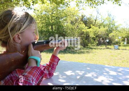 Girl aiming to shoot at target - Stock Image