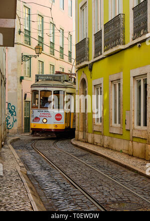 Yellow lisbon tram turning into an extremely narrow street, just wide enough for vehicle - Stock Image