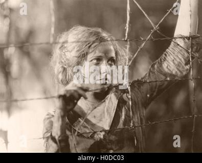 Sad girl behind barbed wire fence - Stock Image