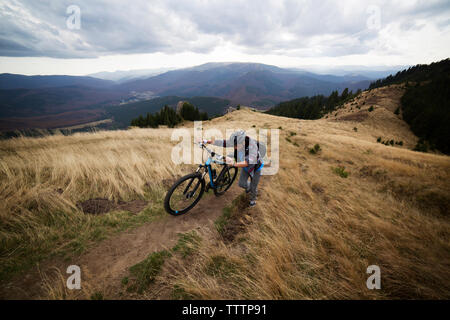 Male backpacker climbing with bicycle on mountain against cloudy sky - Stock Image