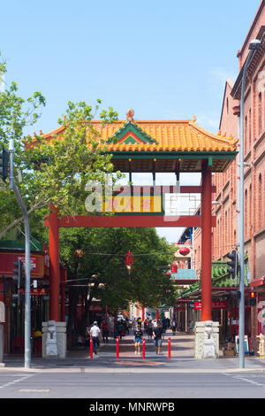 Pedestrians walk through the entrance of Chinatown which features a selection of Asian restaurants and grocery stores in Adelaide, South Australia. - Stock Image