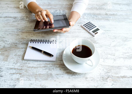 Using the tablet meanwhile drinking coffee - Stock Image
