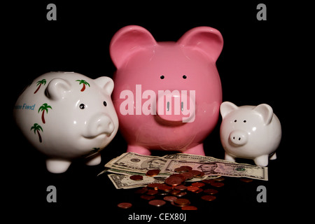 three Piggy Banks with cash on a black background - Stock Image