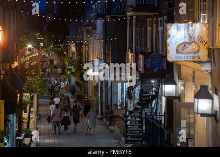 Tourists walking during summer evening on Rue du Petit-Champlain in old Québec City, Canada.  Rue du Petit-Champlain lined with shops and restaurant - Stock Image