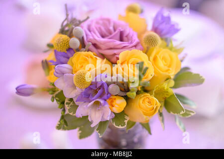 Fancy colored floral arrangement with bright yellow and purple roses as beautiful decor for table centerpieces at weddings or formal events - Stock Image