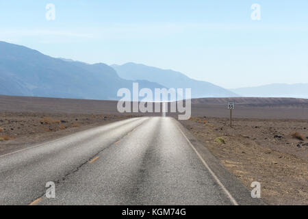 Empty desert road. Death Valley Badwater Road with Badwater Basin shimmering in the distance. - Stock Image
